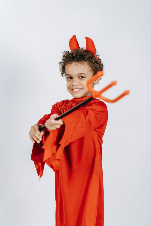 Side view of adorable content African American boy with curly hair wearing red costume of devil and holding artificial pitchfork in hands against white background