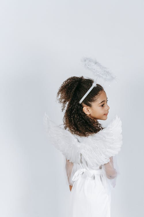 Back view of adorable ethnic little girl with long curly hair demonstrating white wings while standing in studio in angel costume