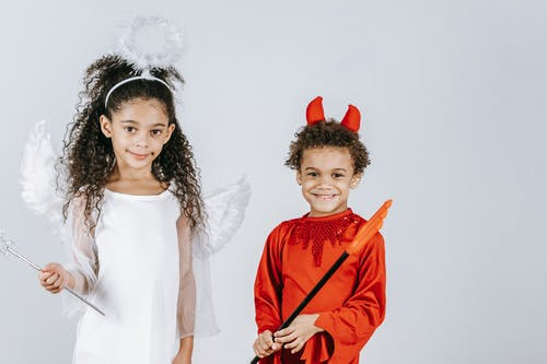 Cute little black children in angel and devil costumes smiling at camera in white studio