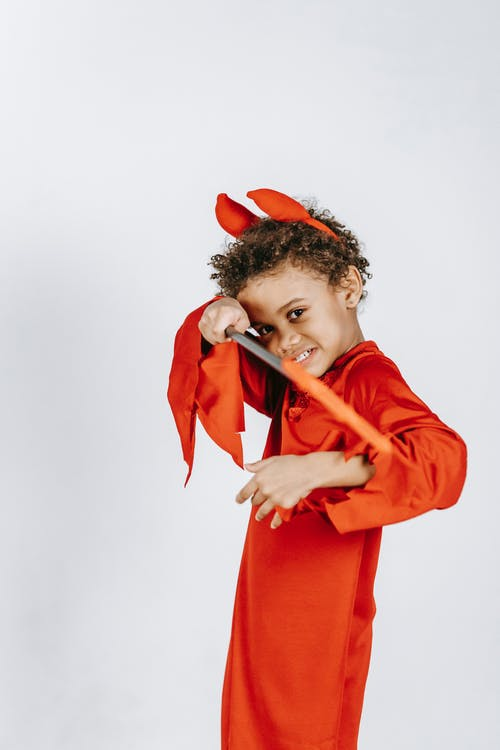 Side view of cheerful little black boy with Afro hair in red devil costume and horns standing against white background with pitchfork in hand and looking at camera
