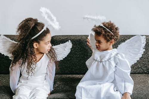 Cute little black siblings in angels costumes playing on couch