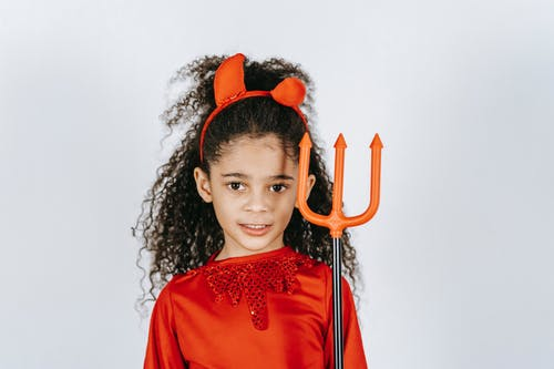 Adorable African American child with long curly hair showing artificial trident while standing in white studio in red Halloween costume of devil