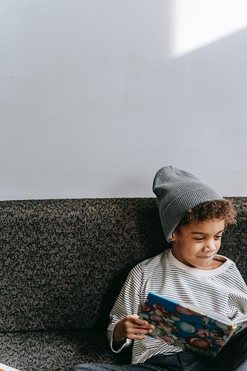 Menino Com Camisa Listrada De Branco E Azul Com Gola Redonda Sentado No Sofá Preto