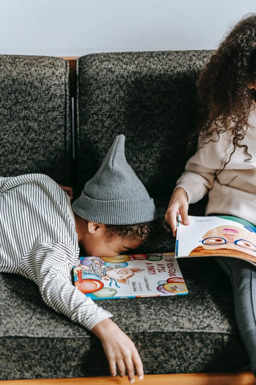 Adorable little black boy in casual clothes and hat lying on couch near crop unrecognizable sister reading fairytale at home