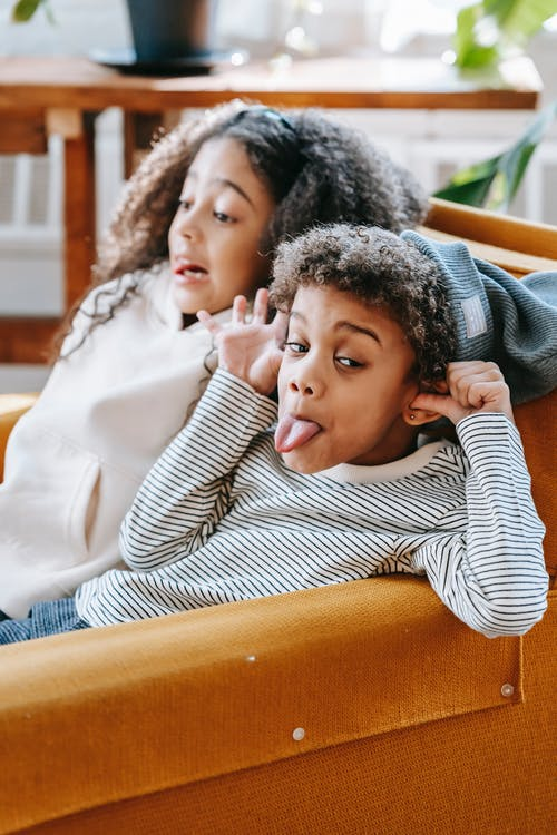 Cheerful little African American children in casual clothes sitting on cozy sofa and showing tongues while having fun together during weekend at home