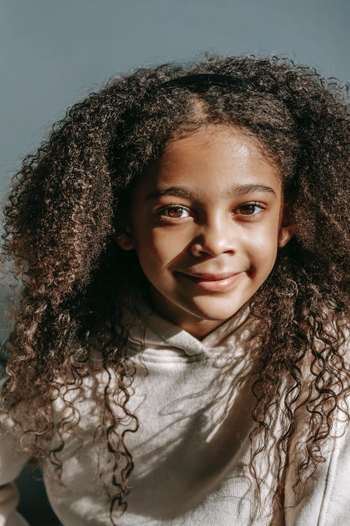Positive adorable little African American girl with long curly hair in hoodie looking at camera against gray background in sunlight