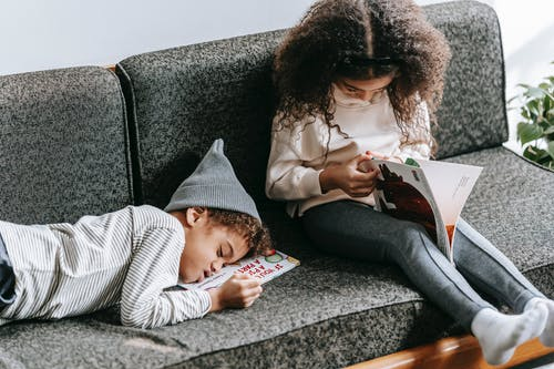 High angle of cute African American kid in casual clothes sleeping on sofa near focused sister studying interesting book during weekend at home