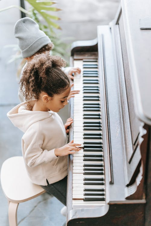 From above side view of attentive little African American girl with curly hair in stylish hoodie sitting on chair and playing piano with unrecognizable sibling