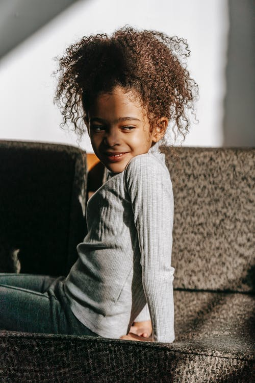Side view of content little African American child with dark curly hair in casual clothes relaxing on comfortable sofa and looking away