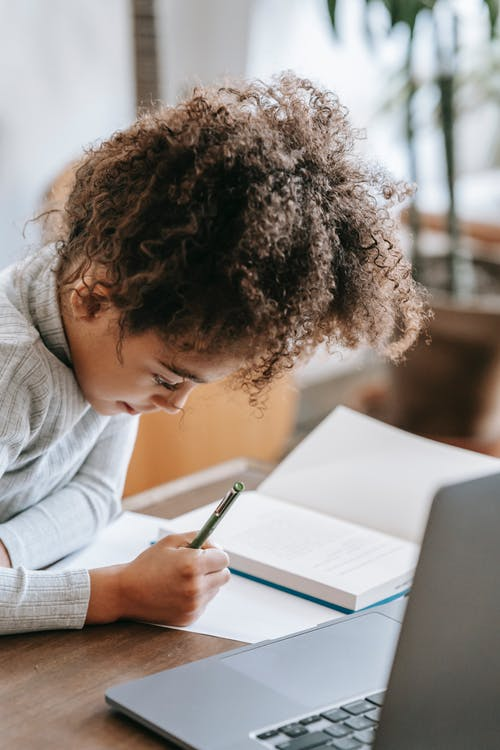 Side view of thoughtful African American schoolgirl with curly hair writing in notebook while sitting at table with laptop and doing homework assignment with concentration