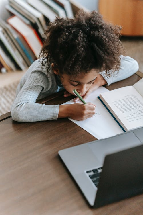 Attentive little ethnic girl writing and browsing laptop while doing homework