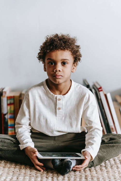 Pensive cute little African American boy with curly hair in casual clothes sitting on floor near stack of books and looking at camera while using tablet at home