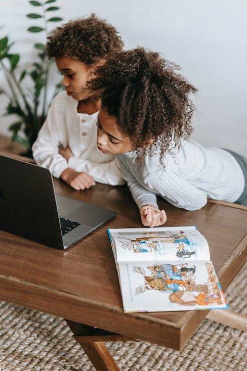 Calm black children sharing laptop at home
