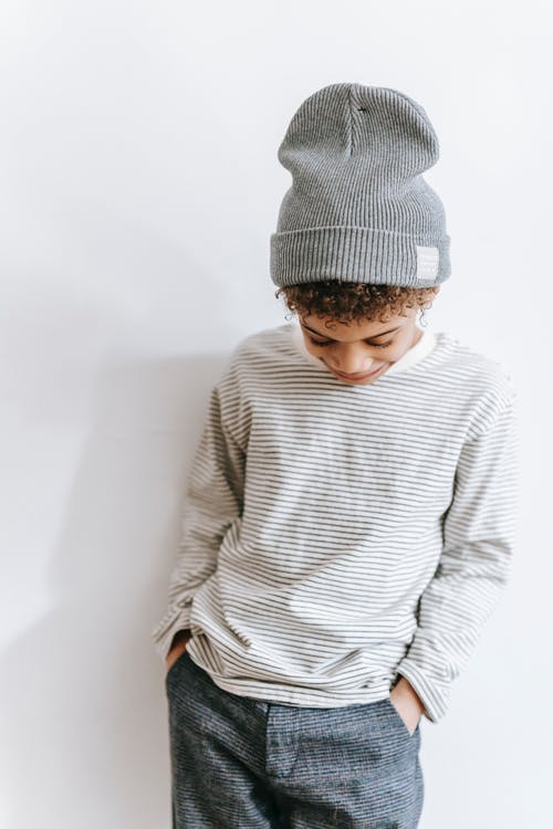 Calm African American boy in trendy outfit standing with hands in pockets and looking down against white wall in room