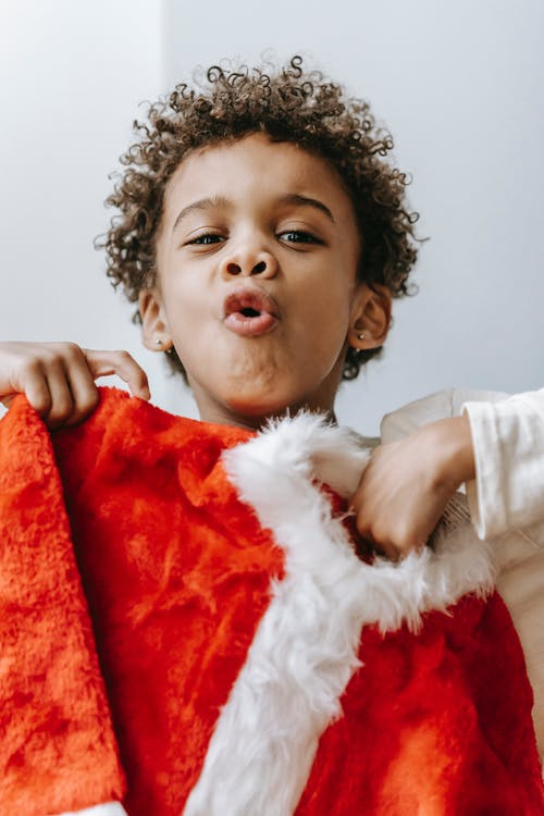 Positive black boy showing Christmas outfit