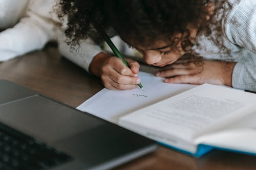 Black girl writing on paper while reading book