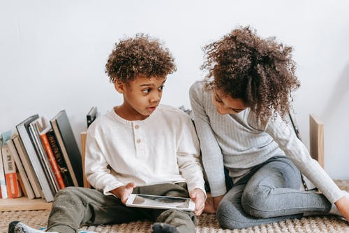 Cheerful black children browsing tablet at home