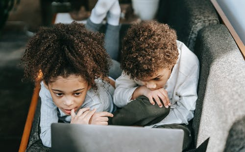 Focused black children watching video on laptop at home