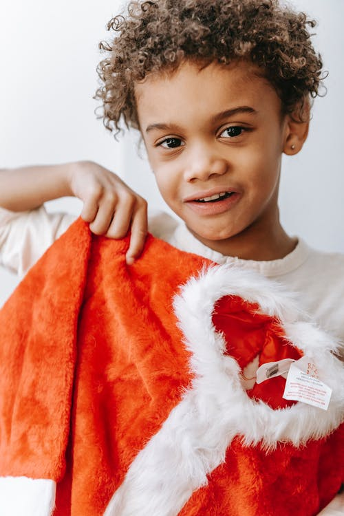Positive African American boy with red Santa Claus costume in hands looking at camera while standing in light room on white background