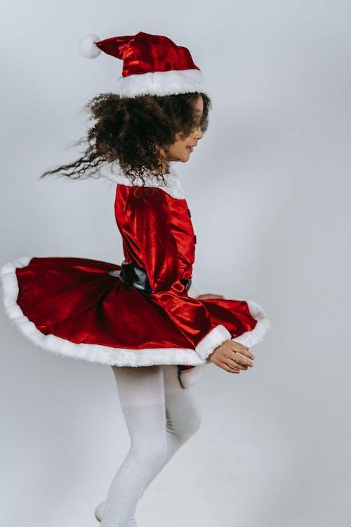 Black girl in red Santa costume dancing