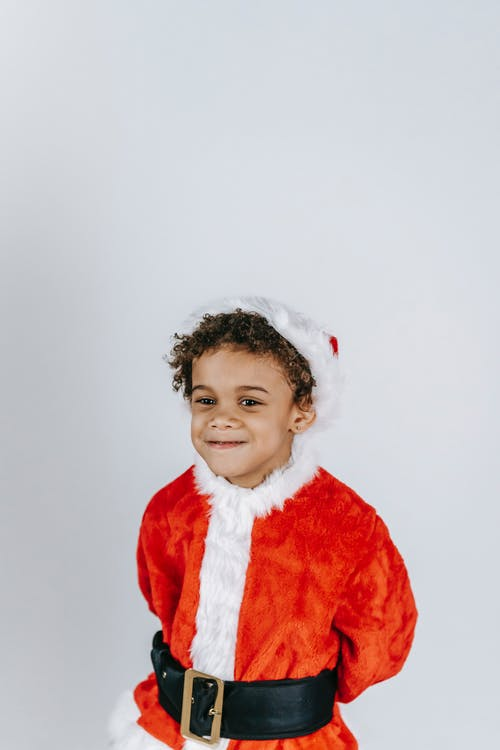 Little African American boy in funny Santa costume smiling and looking away on white background