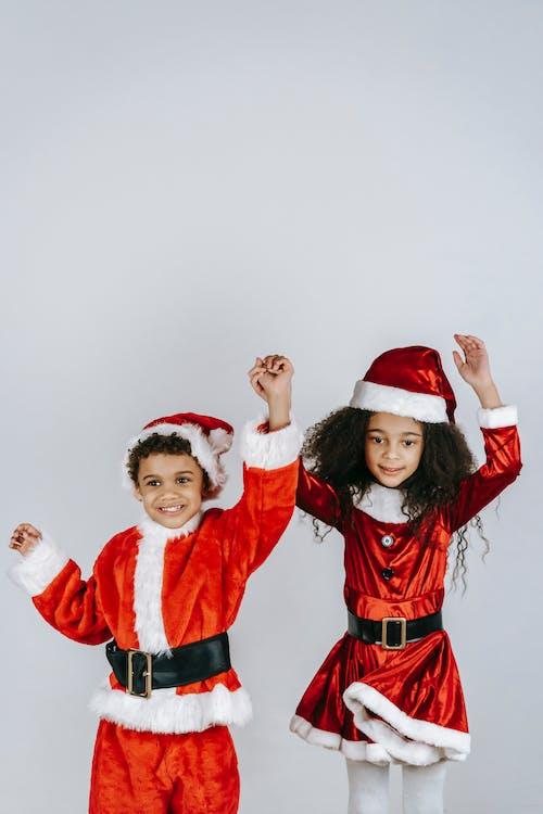 Positive black children in red Santa costumes dancing
