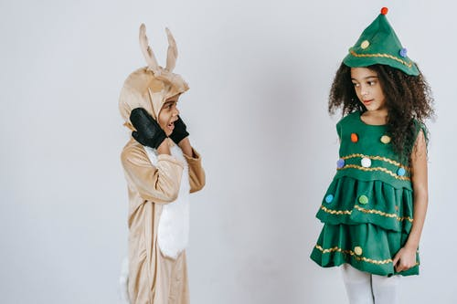 Funny cute African American boy and girl in bright costumes at Christmas party on white background