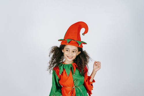 Little black girl in bright costume of elf
