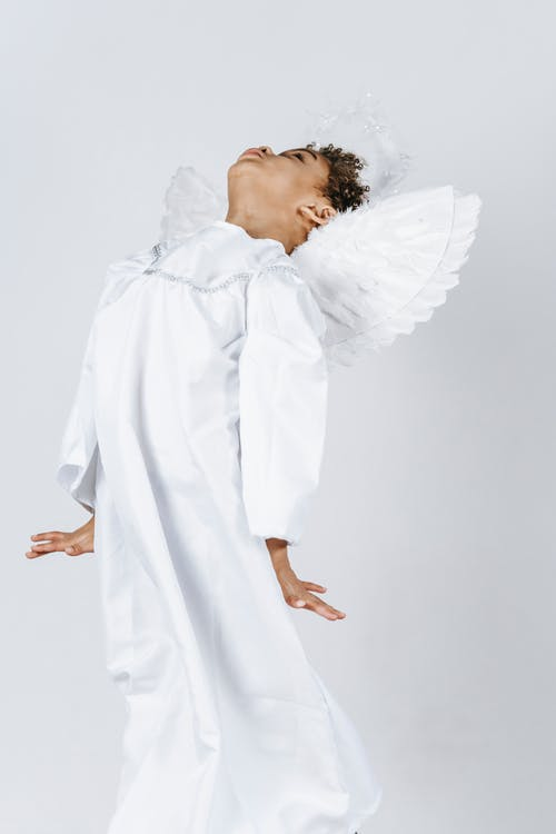 Cute funny African American boy in white costume of angel playing on white background