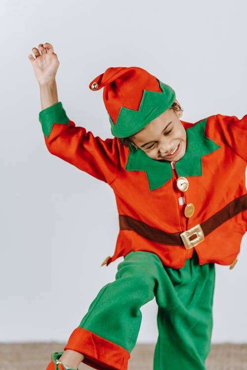Cheerful cute African American boy in red and green costume of elf having fun at Christmas carnival