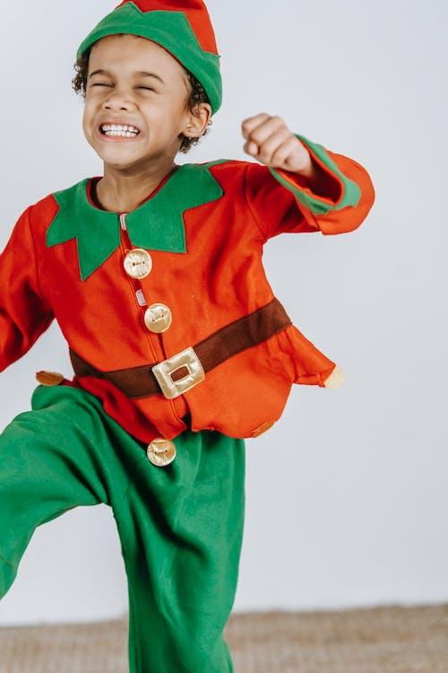 Playful black boy in bright costume of elf
