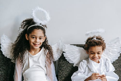 Cheerful African American children in funny costumes of angels with nimbus and wings celebrating Christmas