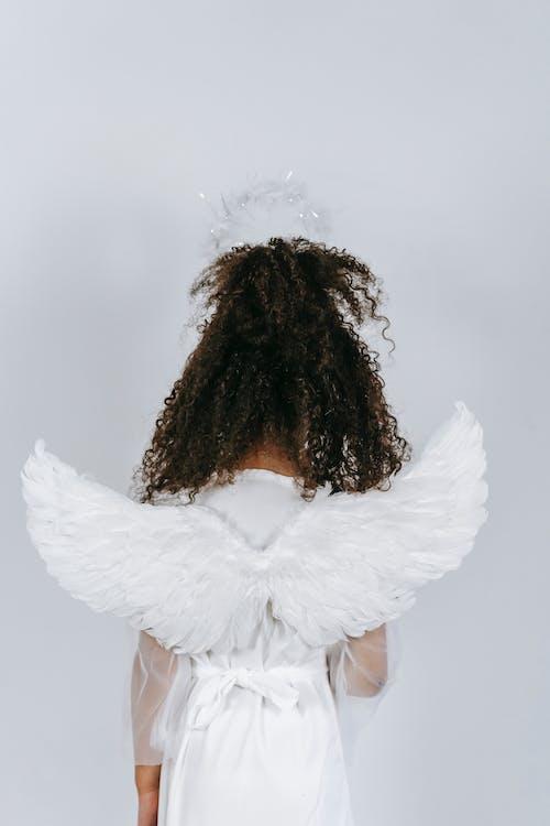 Black girl in costume of angel with tender white wings