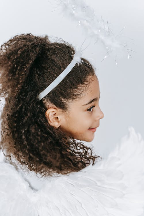 Back view of cute African American girl with gentle wings in costume of angel on white background