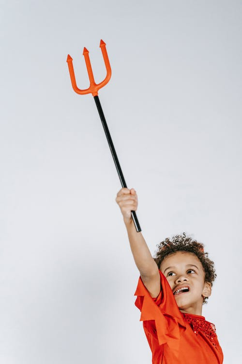 Cute happy black boy in costume of devil playing