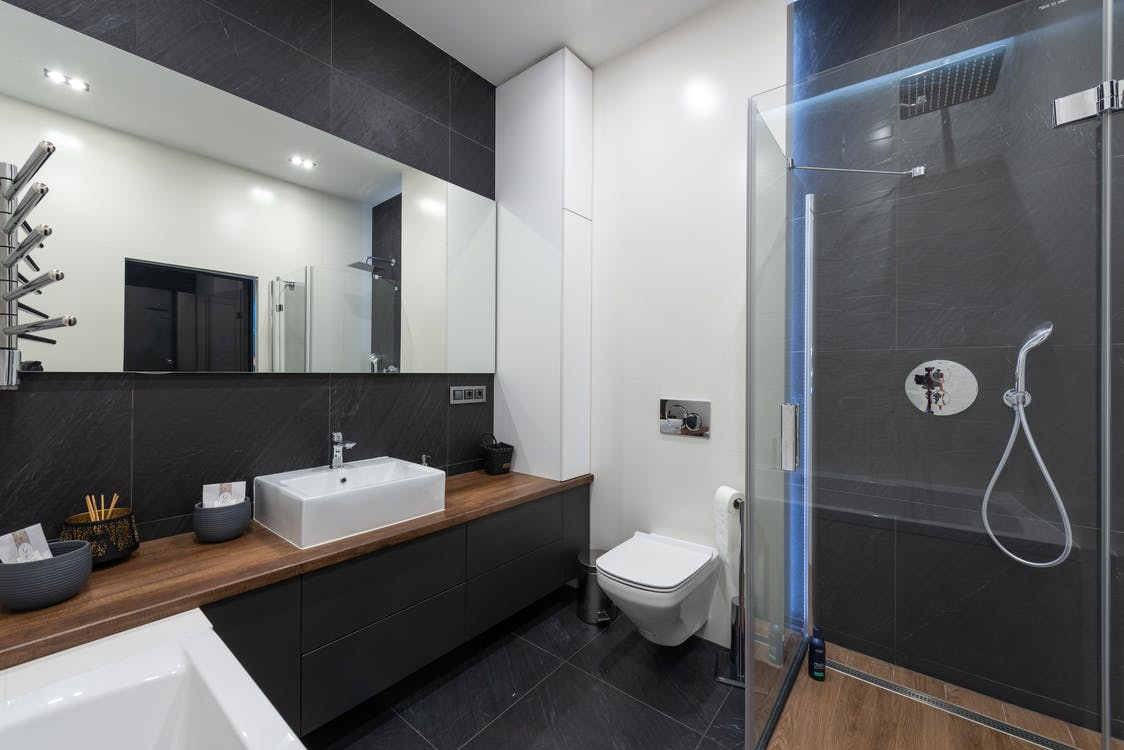 Interior of contemporary washroom with modern transparent shower cabin placed near toilet and sink at mirror with reflection of room