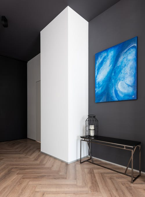 Shelf with decorative element placed on parquet at black wall with creative blue artwork near white column in modern apartment