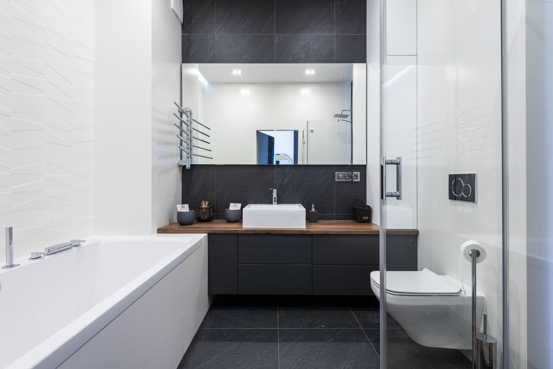 Interior of modern bathroom with bathtub near transparent shower cabin and toilet placed near black cupboard with sink and mirror