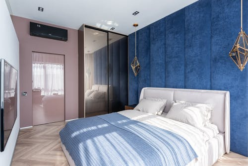 Soft bed with blanket placed against white wall with TV in modern bedroom with wardrobe and door near blue wall
