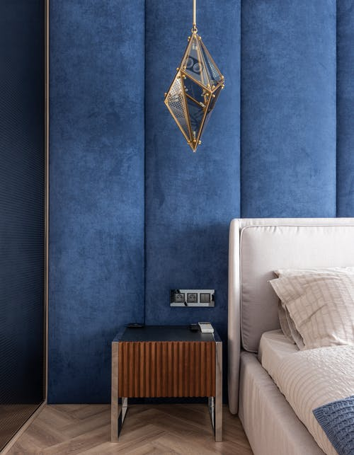 Part of comfortable bed with cushions and blanket placed near blue wall and bedside table in modern bedroom with hanging decoration