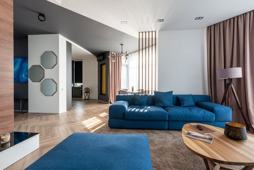 Interior of spacious flat with blue sofa and pouf near wooden table placed on carpet near wall with stylish decorations