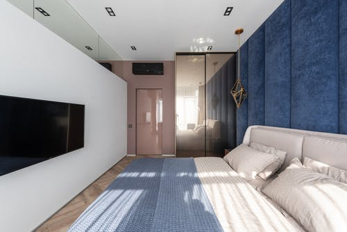 Comfortable bed with pillows and blanket placed near blue wall against contemporary TV in modern bedroom with wardrobe and door