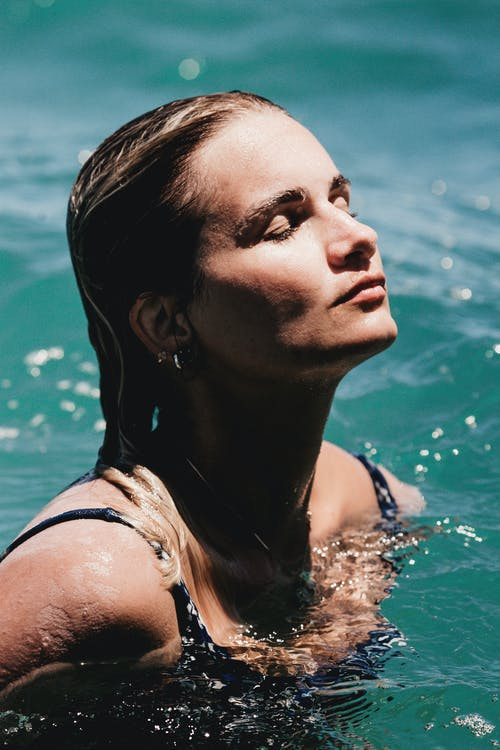 Relaxed female with wet hair and eyes closed swimming in clean transparent water in summer