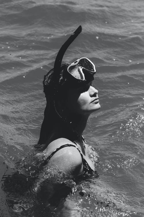 Black and white of female with diving equipment relaxing in wavy water of sea in daytime
