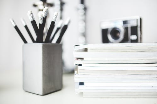 Stack of magazines & pencils in gray cup