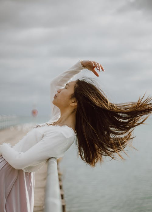 Asian tourist with flying hair on embankment against sea