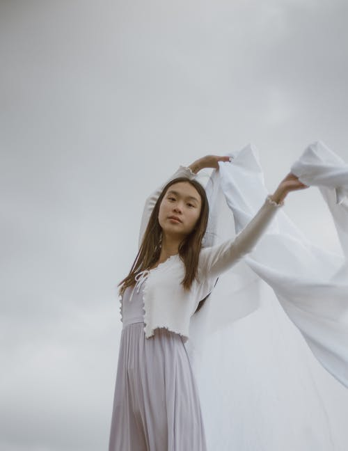 Young tender ethnic female in casual apparel with raised arms and wavy textile looking at camera