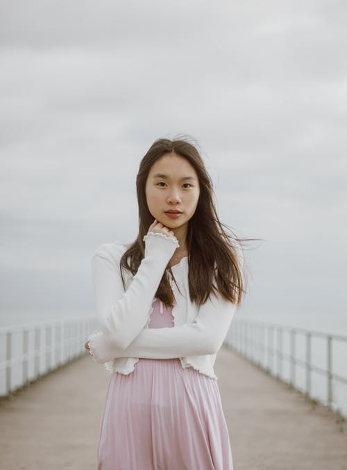 Young tender ethnic female tourist in casual clothes touching chin and looking at camera on fenced embankment between sea