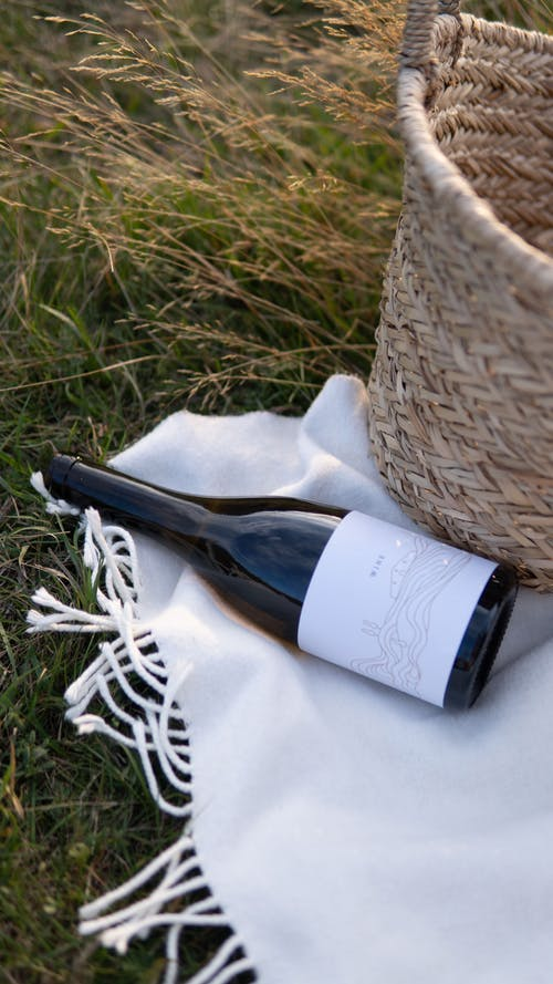 Wine bottle and basket placed on plaid during picnic in nature