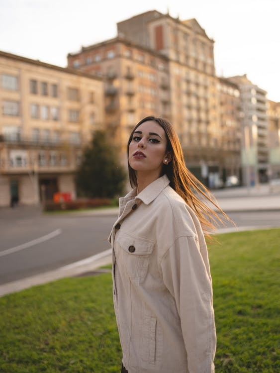 Side view of self assured young lady with long dark hair in trendy outfit standing at roadside near modern building and looking at camera
